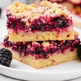 close up shot of Blackberry Pie Bars stacked on top of each other on a plate with blackberries