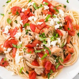 close up overhead shot of bruschetta chicken pasta topped with parsley and feta cheese on a plate
