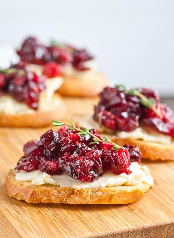 crostini of bread topped with bried and cranberry sauce with a sprig of thyme on top and all sitting on a wood cutting board