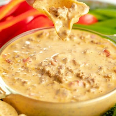 cheese Rotel dip in a bowl with a chip being dipped