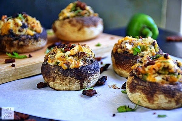 mushrooms with a filling of jalapeno poppers stuffed inside and sitting on a piece of parchment