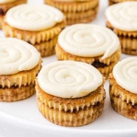 close up shot of mini cinnamon roll cheesecakes on a serving tray