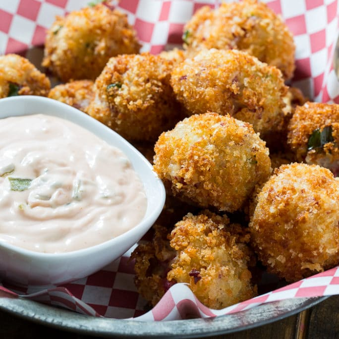 breaded and fried reuben fritters in a basket with a side of dipping sauce