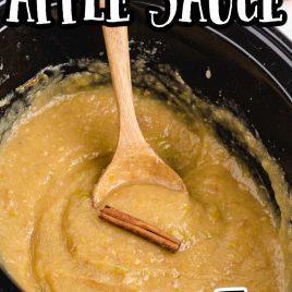 close up shot of crockpot applesauce in a crockpot with a cinnamon stick