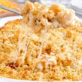 close up shot of Million Dollar Mac and Cheese in a baking dish with a serving being picked up with a large spoon