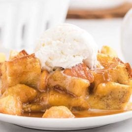 close up shot of a slice of Peach Bread Pudding topped with vanilla ice cream on a plate