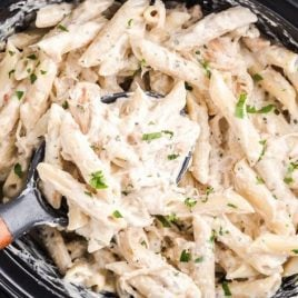 close up shot of Slow Cooker Olive Garden Chicken Pasta topped with parsley in a crockpot