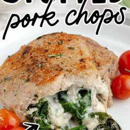 close up shot of Stuffed Pork Chops with cherry tomatoes and spinach on a plate