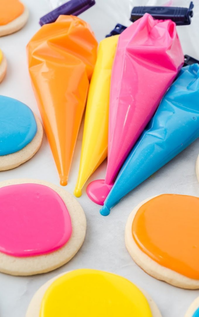 yellow, pink, blue, and orange icing in piping bags and also on top of sugar cookies