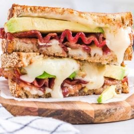 close up shot of slices of a bacon avocado sandwich stacked one top of each other on a wooden board
