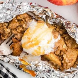 close up shot of campfire apple crisp in aluminum foil topped with vanilla ice cream and caramel syrup