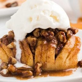 close up shot of hasselback apples topped with pecans and vanilla ice cream on a plate