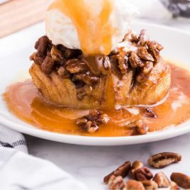 close up shot of hasselback apples topped with caramel, pecans, and vanilla ice cream on a plate