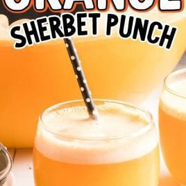 Orange sherbet in a glass with straw and also a serving bowl full of orange sherbet in background