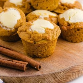 muffins on a board with cinnamon sticks on the side