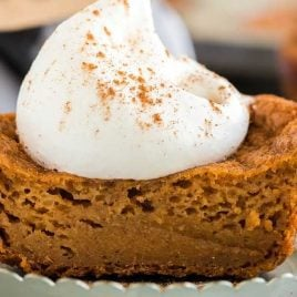 close u shot of half of a pumpkin cupcakes topped with whipped cream and cinnamon