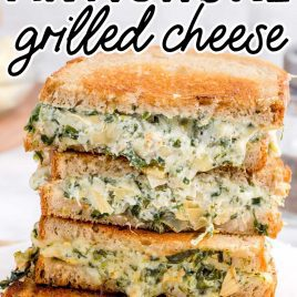 close up shot of slices of spinach artichoke grilled cheese stacked on top of each other on a wooden board