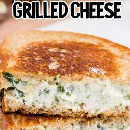 close up shot of slices of spinach artichoke grilled cheese stacked on top of each other on a plate