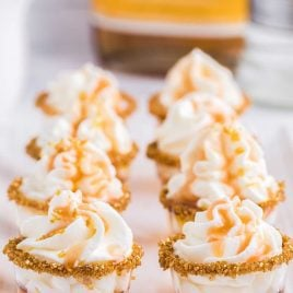 close up shot of Butterbeer Jello Shots topped with whipped cream and caramel topping on a plate
