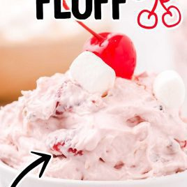 close up shot of a serving of Cherry Fluff topped with mini marshmallows and a cherry in a bowl