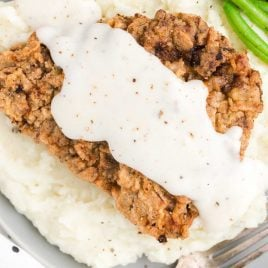 close up overhead shot of Chicken Fried Steak topped with homemade gravy and served with mashed potatoes and green beans