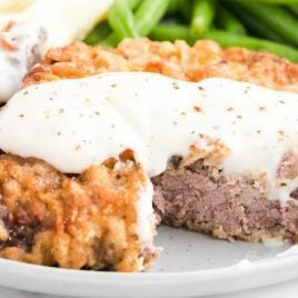close up shot of Chicken Fried Steak topped with homemade gravy and served with mashed potatoes and green beans on a plate with a piece of the steak taken out by a fork