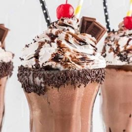 close up shot of glasses of Chocolate Milkshake topped with whipped cream then garnished with Hershey bars, a cherry, chocolate sprinkles, and chocolate syrup