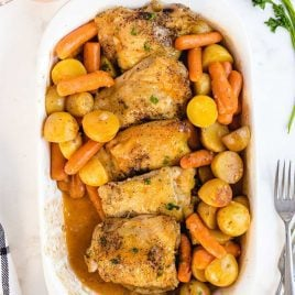close up overhead shot of a baking dish of Crockpot Chicken Recipe served over potatoes and carrots