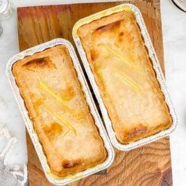 close up overhead shot of aluminum foil pans of Freezer Chicken Pot Pies on a wooden board