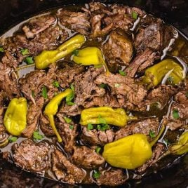 close up overhead shot of Mississippi Pot Roast with pepperoncinis and garnished with parsley in a crockpot