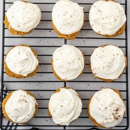 close up overhead shot of Pumpkin Cookies with Cream Cheese Frosting sprinkled with cinnamon on a cooling rack