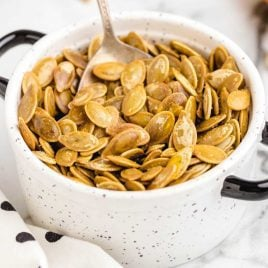 close up shot of a bunch of Roasted Pumpkin Seeds in a bowl with a spoon