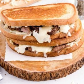 close up shot of Steak Grilled Cheese sandwiches stacked on a wooden board