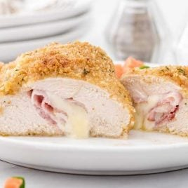 close up shot of pieces of chicken cordon bleu served with vegetables on a plate