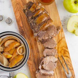 close up overhead shot of crockpot apple pork tenderloin diced on a wooden board