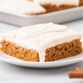close up shot of a slice of pumpkin sheet cake with icing on a plate