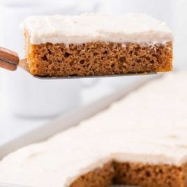 close up shot of a slice of pumpkin sheet cake with icing on a spatula