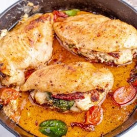 close up shot of sun dried tomato stuffed chicken in a skillet with tomato slices and spinach