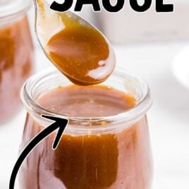 close up shot of Caramel Sauce in a jar with a spoonful of sauce being scooped out of the jar