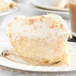 close up shot of a slice of Coconut Cream Pie on a plate with a fork