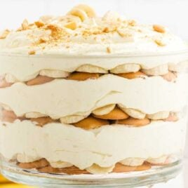 close up shot of a bowl of copycat magnolia banana pudding topped with banana slices and crushed vanilla wafers