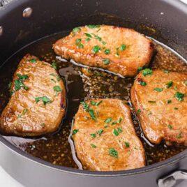 close up shot of a pot of Honey Garlic Pork Chops garnished with parsley