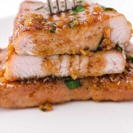 close up shot of Honey Garlic Pork Chops garnished with parsley and stacked on top of each other