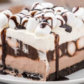 close up shot of a slice of Hot Chocolate Lasagna topped with mini marshmallows and drizzled with chocolate syrup on a plate