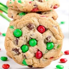 close up shot of M&M Christmas Cookies stacked on top of each other with a cookie in the front