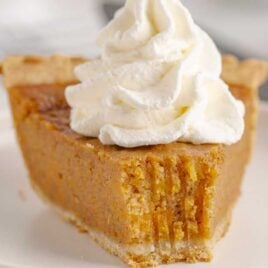 close up shot of a slice of Sweet potato pie topped with whipped cream on a plate
